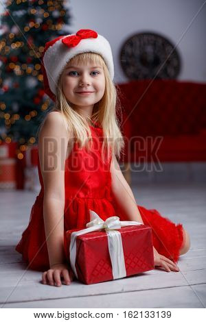 Merry Christmas and Happy Holidays. Cheerful cute little child girl with present. Kid holds a magic gift box near Christmas tree indoors.