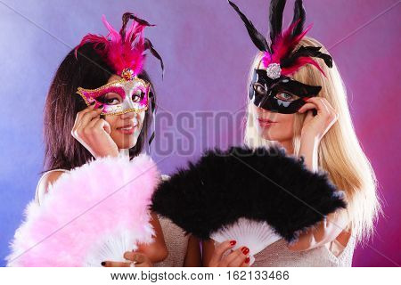 Holidays people and celebration concept. two women mixed race and caucasian with carnival venetian masks and feather fan