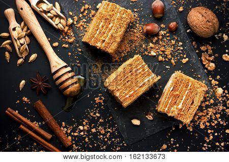Sweet homemade layered honey cake on a black table with spices and nuts
