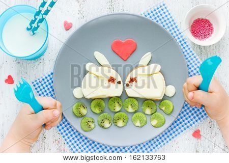 Food art idea for funny kids breakfast or romantic breakfast for lovers on Valentines Day - two enamored cheese toast bunny with kiwi and sweet candy heart