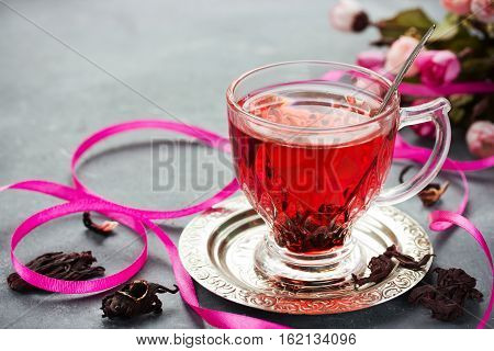 Cup of hot hibiscus tea (karkade red sorrel rosella). Healthy drink from magenta calyces (sepals) of roselle flowers