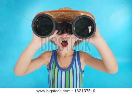 Curious boy in cowboy hat looking through binoculars. Photo close-up on a blue background
