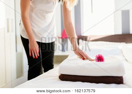 Young Hotel Maid Placing Flower On Fresh Towels