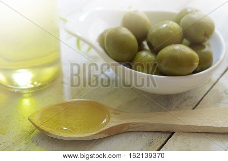 Spoon with olive oil next to an oilcan and some natural green olives. Scene on a wooden white table of a rustic kitchen.