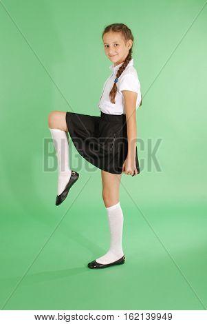 School girl pretty tomboy raising her leg isolated on green