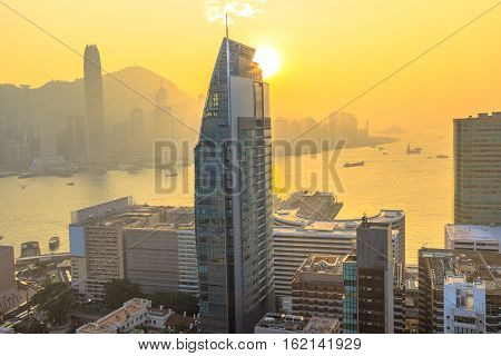 Panoramic scenary of Victoria Harbor, skyscrapers and Hong Kong skyline at sunset.