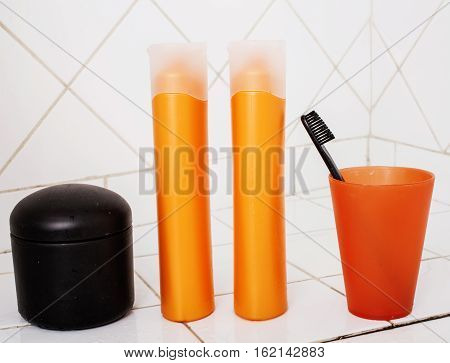 usual stuff in bathroom, shampoo, accessories, black stylish toothbrush, casual normal real background close up poster