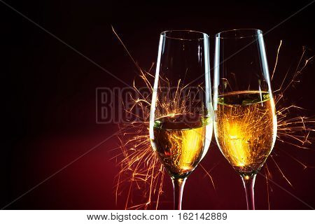 New Year party time with two champagne glasses and fireworks of sparklers against a dark red background with copy space