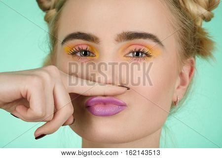 fuh girl with bright makeup making fake mustache on green background