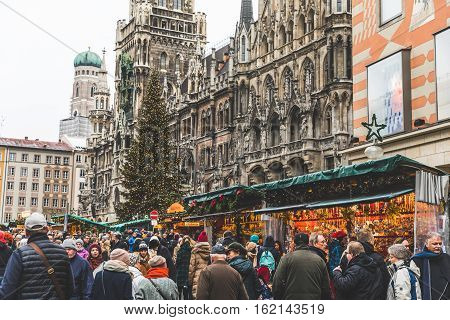 MUNICH GERMANY - DECEMBER 11 2016: Christmas market with a lot of people in Marienplatz the main square of the city. On background there are a tall Christmas tree the new City hall and the Cathedral.