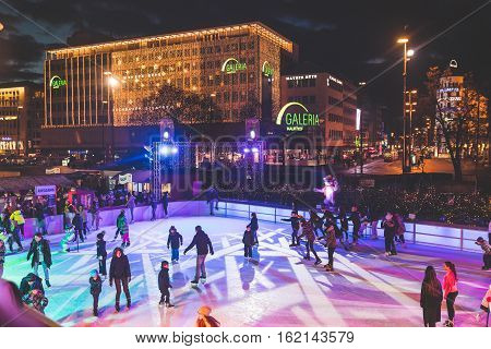 MUNICH GERMANY - DECEMBER 11 2016: People ice skating in Karlsplatz. On Christmas time a large ice rink is available during day and evening in the famous square of the city