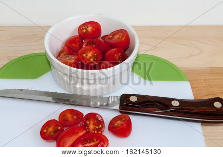 Grape tomatoes on a cuttting board with a white bowel all cut with knife