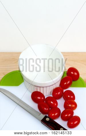 Grape tomatoes on a cuttting board with a white bowel - none cut