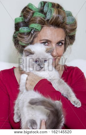 Beautiful Lady With Curlers Stroking The Cat On The Couch