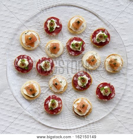 A plate of savoury pikelets in a glass dish.