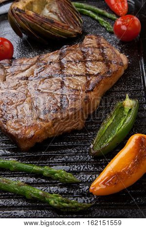 Summer grill - grilled T-bone steak and assorted grilled vegetables - asparagus mini pepper and tomatoes - on griddle.