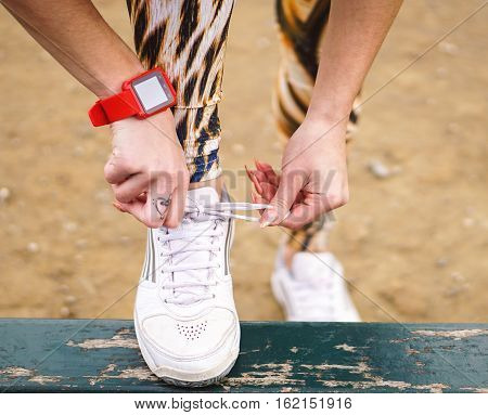 Closeup of female hands tying the laces on her running sneakers - Young sportswoman working out