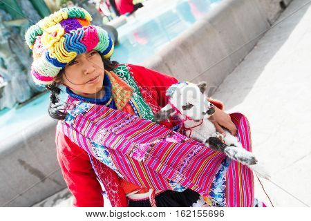 CUSCO - SEPTEMBER 02: Close-up of unknown local peruvian girl with lamb on background of tourists locals and architectural details on the streets of Cusco Peru on September 2nd 2016.