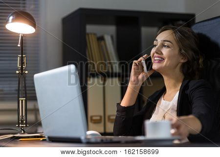 Portrait of a  businesswoman sitting at her workplace in office and talk to phone