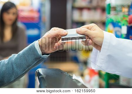 Man using a credit card to pay in a grocery store