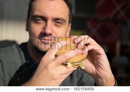 Man eating an hamburger in a fast food