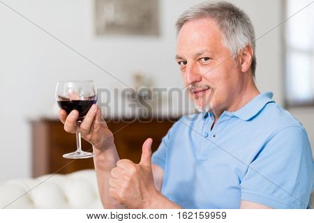 Mature man drinking a glass of red wine at home and giving thumbs up