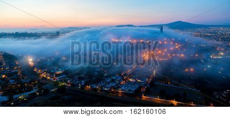 Early morning fog over the rising city of Queretaro Mexico. The aqueduct of Queretaro, is currently building a monumental seventy four arches reaching an average height of twenty eight meters.