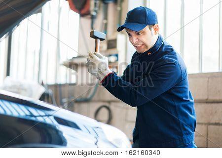 Angry mechanic smashing a car engine