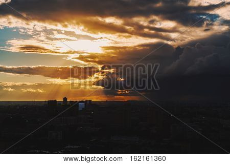 Dramatic yellow and orange scenery of the city silhouette at sunset after storm with massive cloud front and sun god rays