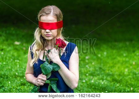 beautiful girl blindfolded holding a red rose in the park