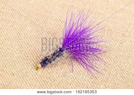 Close Up of Colorful Fishing Fly on Burlap Background