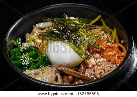 Korean soup with egg and seaweed in black dish