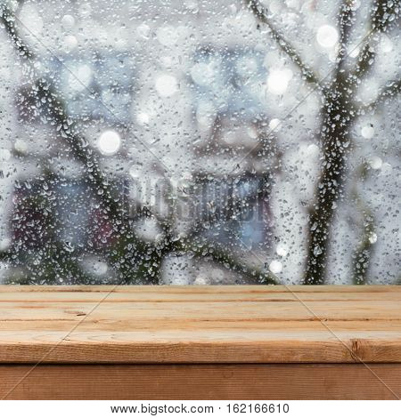 Empty wooden deck table over wet glass window. Rainy weather concept. Background for product montage display