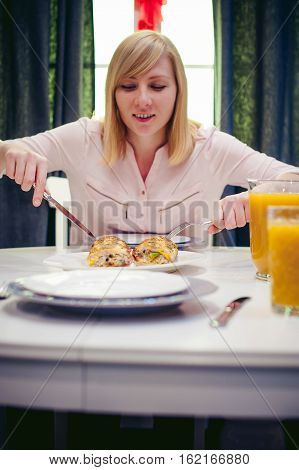 Pretty Blonde Woman In A Pink Shirt, Eating At Home A Fork And Knife. Breakfast Sandwich And Peach J