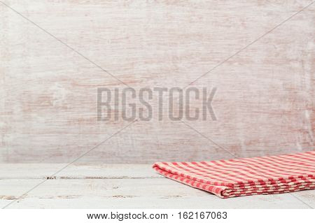 Empty wooden table with checked tablecloth over rustic wall. Background for product montage display