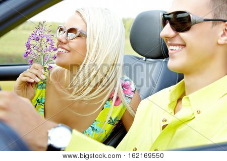 Young woman smelling flowers in the car of her boyfriend