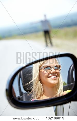 Girl in a rear-view mirror looking at the road