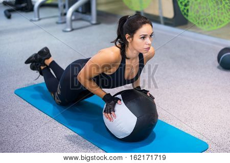 Fit woman exercising with medicine ball workout out arms Exercise training triceps and biceps doing push ups. poster