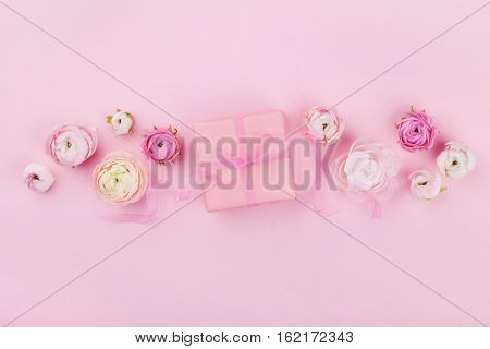 Gift or present box and spring flower on pink desk from above for wedding mockup or greeting card on womans day in flat lay style.
