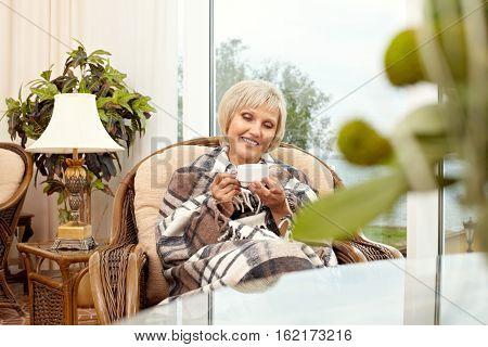 Senior woman drinking tea wrapped in plaid