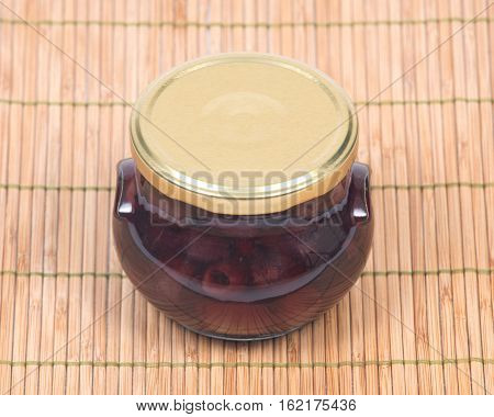 Jumbo pitted kalamata olives in jar on bamboo placemat