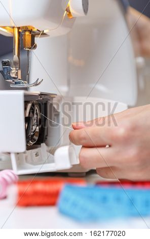 Woman put thread in sewing-machine