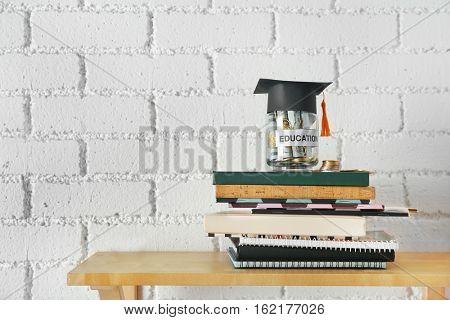 Glass jar with money for education, books and notepads on wooden shelf