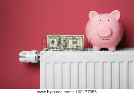 Savings concept. Piggy bank and money on heating radiator with temperature regulator on pink background