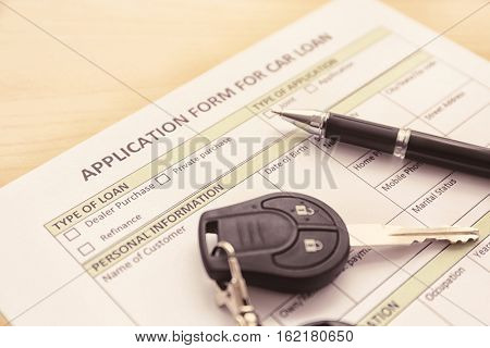 Application form for car loan, pen and key on wooden table, close up view
