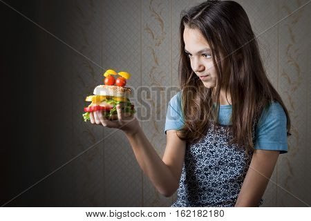 11 year old girl holding at arm hamburger decorated as smiley face with eyes of cherry tomatoes and looks at it.
