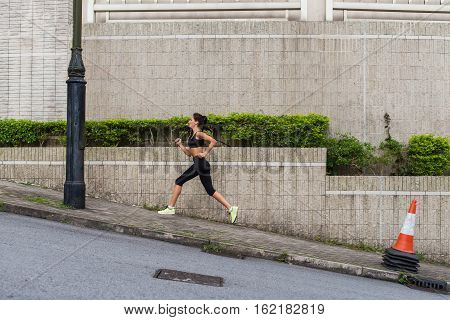 Female runner running uphill on town street. Sporty young woman doing cardio exercises outdoors