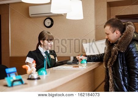 Side view of female receptionist and male guest standing at hotel reception and  paying with check during check-in