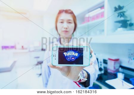 Chiangrai Thailand - August 16th 2016 : Asia woman medical technician holding a smart phone and show Pokemon Go logo in hospital laboratory a free-to-play augmented reality mobile game developed by Niantic for iOS and Android devices.