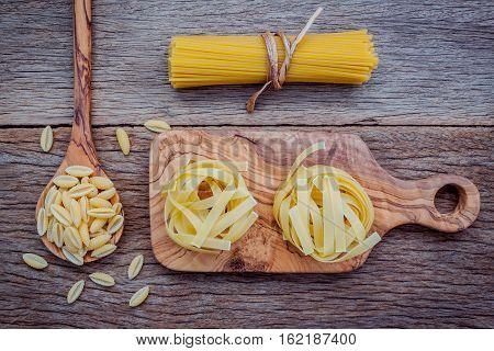 Various Kind Of Pasta Fettucini ,spaghetti And Orecchiette Pugliesi On Cutting Board Setup On Shabby